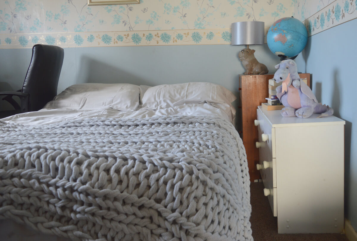 A knitted throw on a double bed beside a chest of drawers
