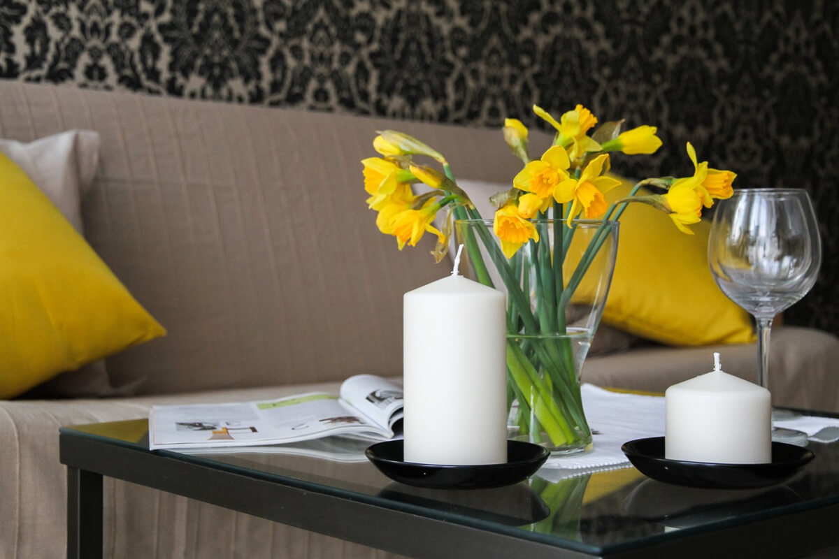 Daffodils in a vase on a glass table beside a large and small white candle and empty wine glass