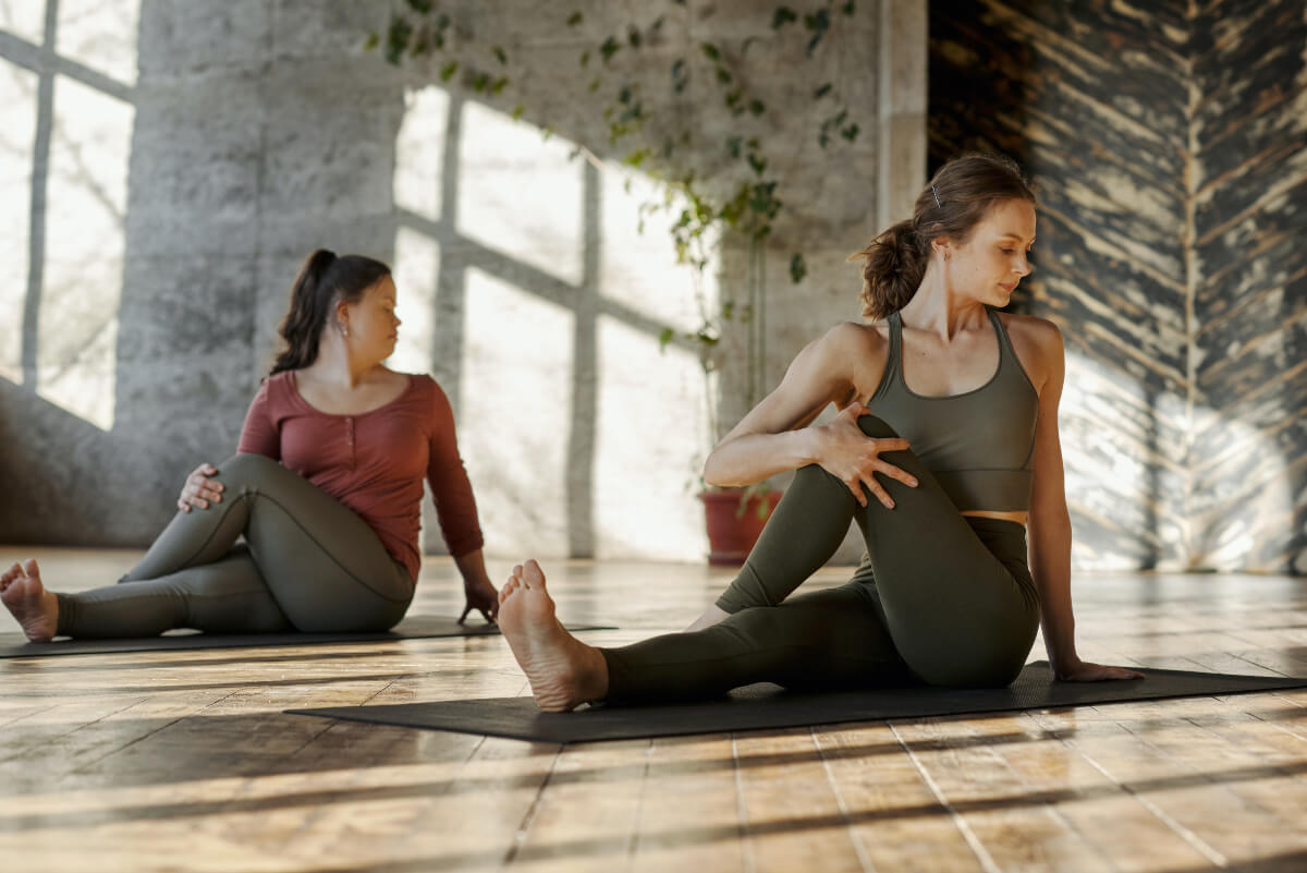 two ladies doing yoga stretches in a studio on a wooden floor