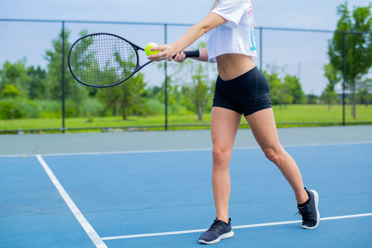 Woman playing tennis on a blue court