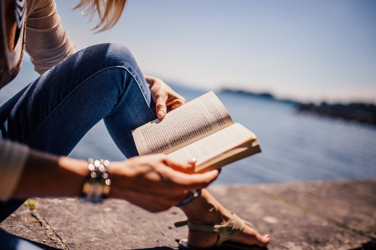 Girl reading book beside the sea
