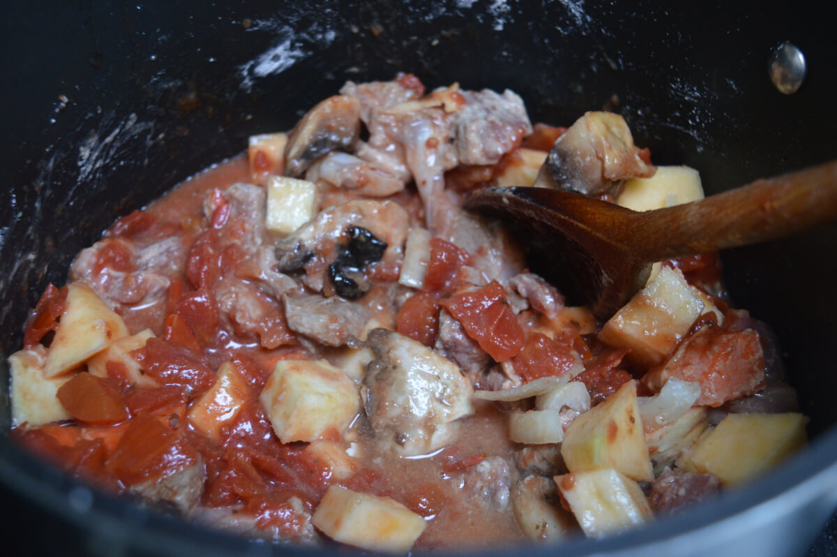 lamb and casserole vegetables in a pan with flour, tomatoes and stock