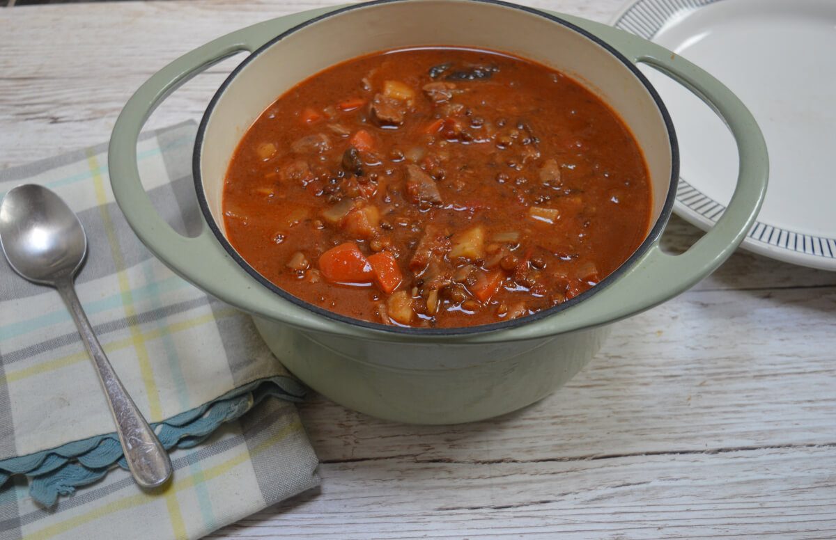 Lamb and lentil stew in a casserole dish on a table. There is a spoon and plate beside the dish.