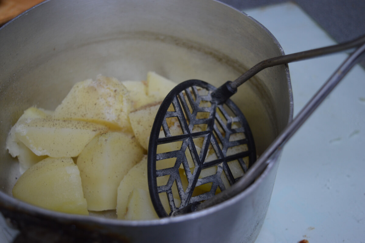 Potatoes in a pan being mashed