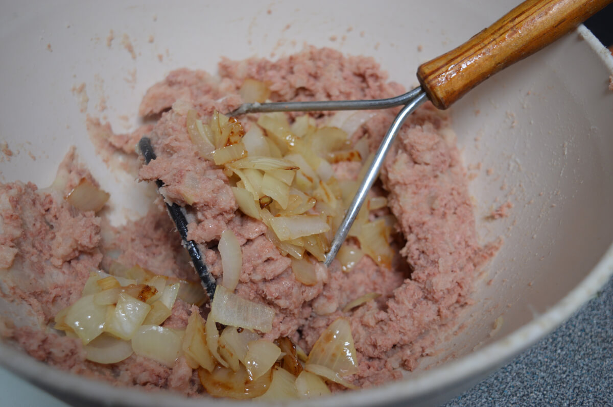 Onions added to mashed corned beef and potato in a bowl.