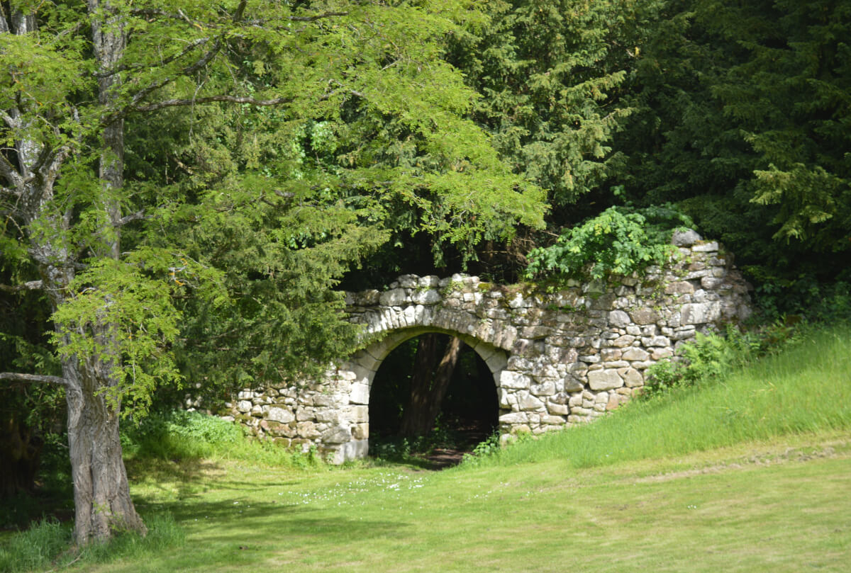 The grounds of Chillingham castle, a wall beside a tree with a tunnel in it