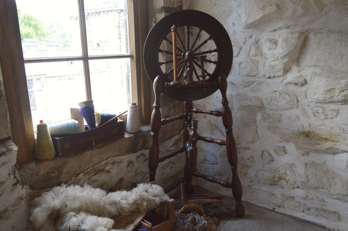 A spinning wheel on a narrow stairway with lots of wool in a box beside it