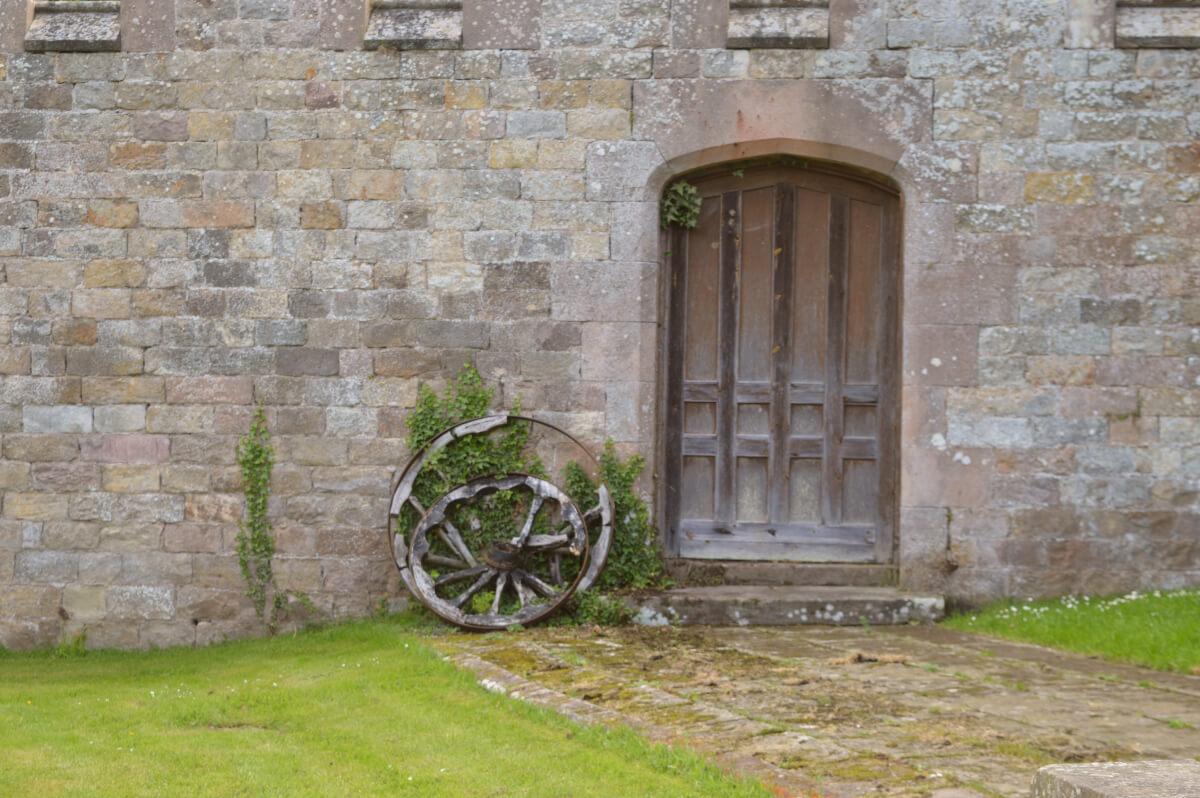 Castle door with wagon wheels beside it
