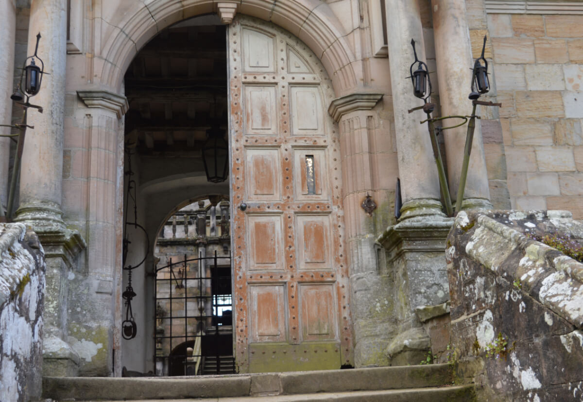 The entrance into Chillingham castle, some stone steps leasding to a wooden door.