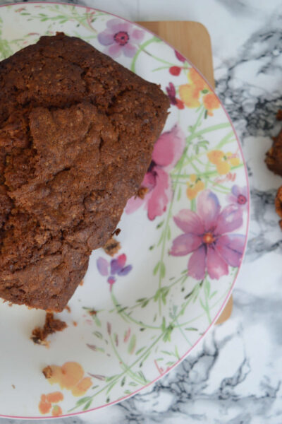 Banana and walnut bread. Two slices cut off beside the loaf on a flowery plate