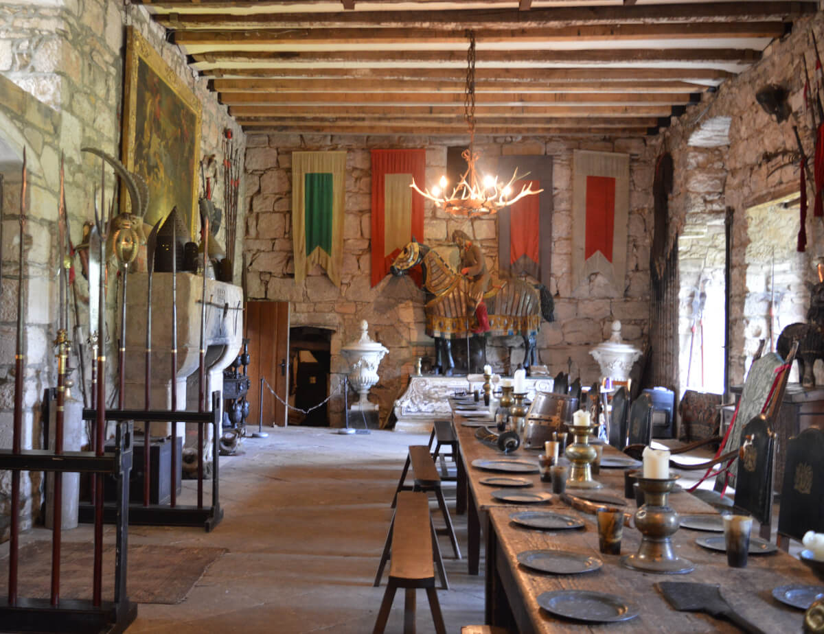 Chillingham castle great hall.  A wooden table is set for a feast, mounted armour stands agains the wall under banners and weapons are on display.
