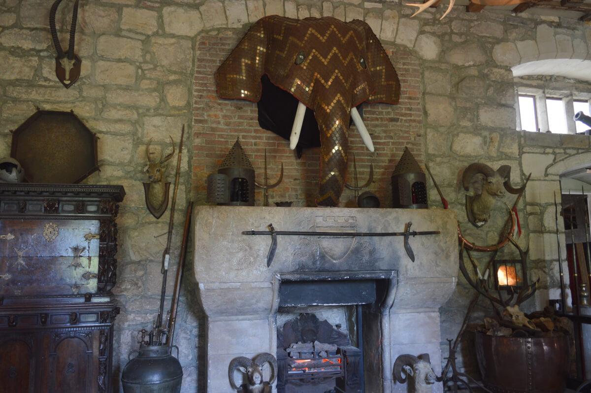 A stone fireplace with a decorative elephants head above it