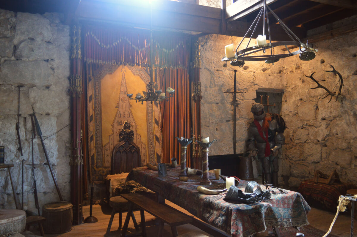 King Edward I room. Weapons and deer antlers hang from the walls. A suit of armour is in the corner and a wooden table is in the middle of the room