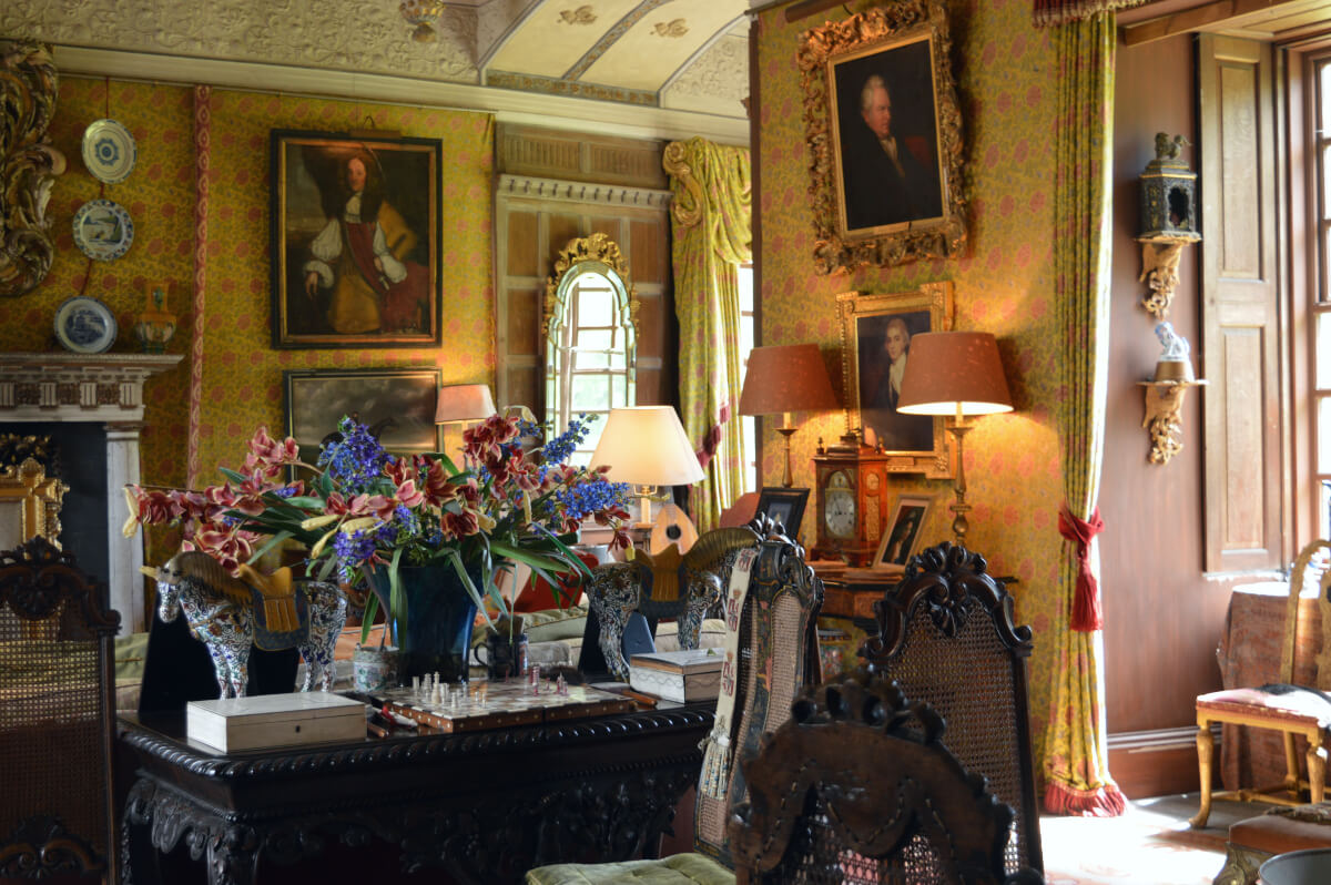 King James I room at Chillingham castle. Gold wallpaper with pink roses is on the walls alongside paintings. A display of flowers is on a desk with a chessboard