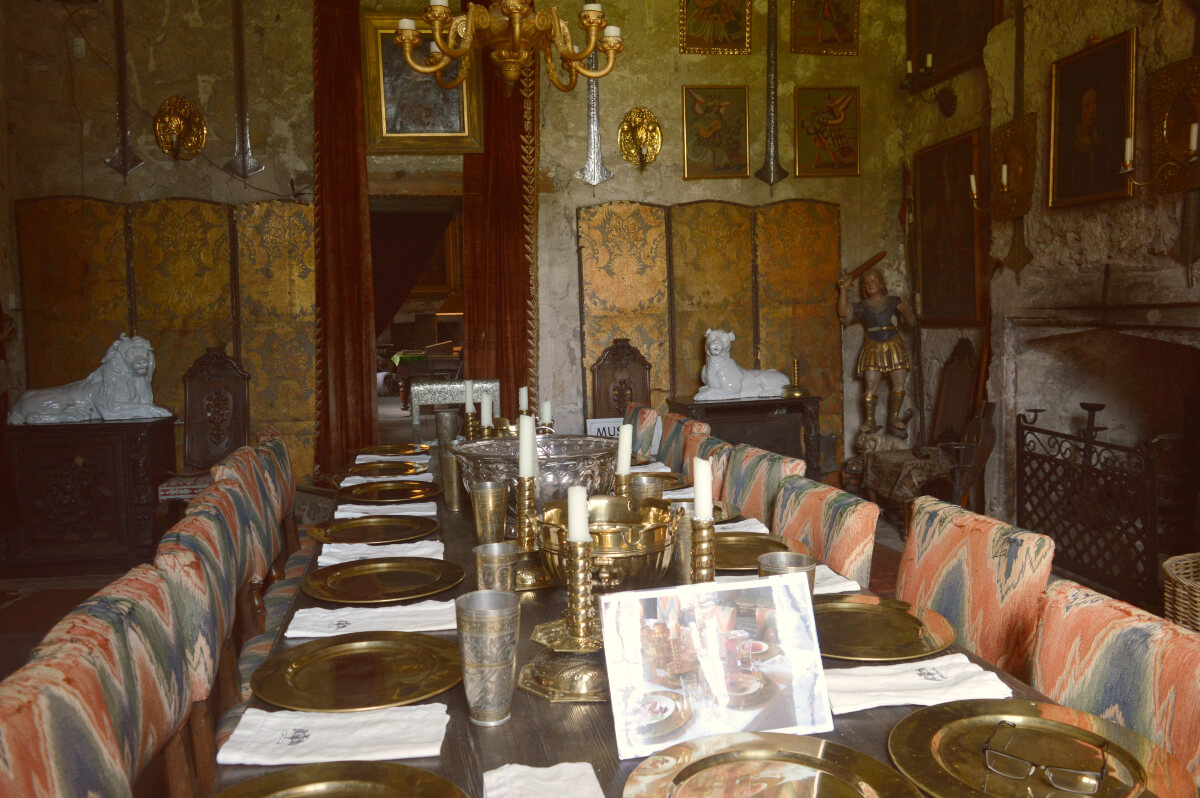 The dining room at Chillingham castle. A long wooden table is set for dinner