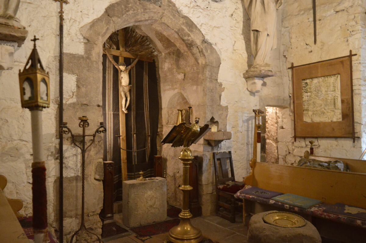 The chapel at Chilingham castle. A gold eagle lecturn is in front of a cross