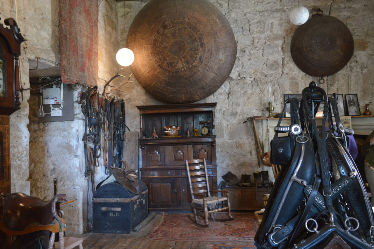 The still room, giant pots hang on the wall, a wooden rocking chair is in the corner and horse tackle hangs from hooks.